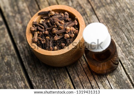 Essential oil of cloves and cloves spice on wooden table. #1319431313