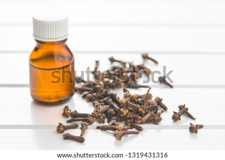 Essential oil of cloves and cloves spice on wooden table. #1319431316