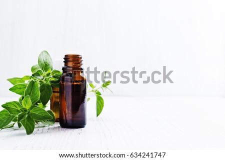 Essential oil of oregano in dark bottles, fresh green mint on white wooden background, selective focus . #634241747