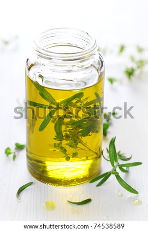 Essential Oil with rosemary and fresh herbs on white wooden background