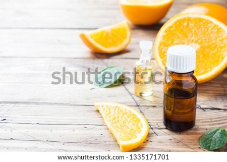 Essential orange oil in bottle, fresh fruit slices on wooden background. Natural fragrances #1335171701
