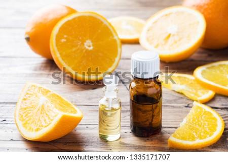 Essential orange oil in bottle, fresh fruit slices on wooden background. Natural fragrances #1335171707