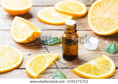 Essential orange oil in bottle, fresh fruit slices on wooden background. Natural fragrances #1335171752