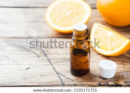 Essential orange oil in bottle, fresh fruit slices on wooden background. Natural fragrances #1335171755