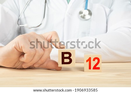 essential vitamins and minerals for humans. doctor recommends taking vitamin b12. doctor talks about the benefits of vitamin b12. B12 Vitamin - Health Concept. B12 alphabet on wood cube.