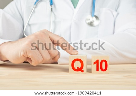 essential vitamins and minerals for humans. doctor recommends taking vitamin coenzyme q10. doctor talks about the benefits of vitamin q10. Vitamin - Health Concept. q10 alphabet on wood cube.