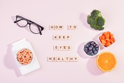 Essential vitamins and supplements to keep eyes healthy on pink background. Eyeglasses, vitamin pills, food containing vitamins for good eyesight with text healthy eyes, top view, pink table top