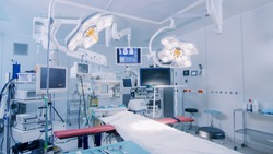 Establishing Shot of Technologically Advanced Operating Room with No People, Ready for Surgery. Real Modern Operating TheaterWith Working equipment,  Lights and Computers Ready for Surgeons.