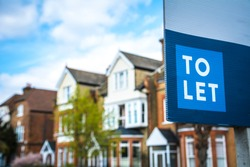 Estate agency 'To Let' sign board with large typical British houses in the background