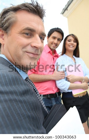 Estate-agent about to show couple round a property
