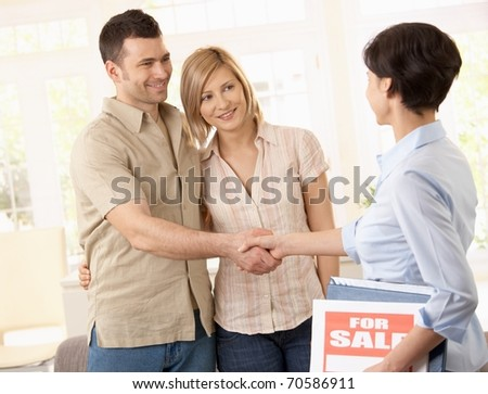 Estate agent congratulating young couple on making deal on new house.? - stock photo