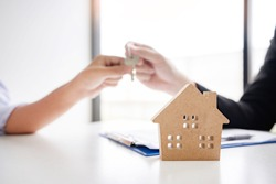 estate agent giving house keys present price for loan investment to home ownership for buy house contract.