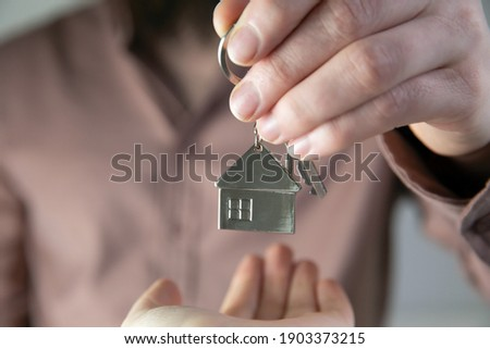 Estate agent giving house keys to client for new home, contract real estate for mortgage approved, focus on keys, business, financial, Estate concept close to