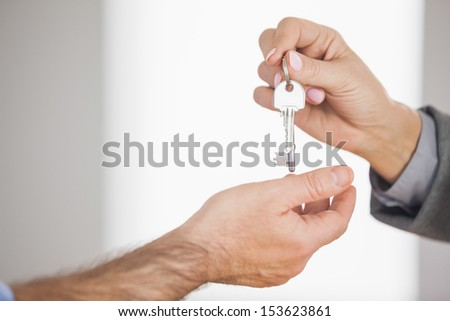 Estate agent giving key to customer in an empty house