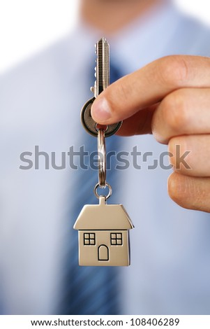 Estate agent holding out house keys on a silver house shaped keychain concept for moving, selling or buying a house