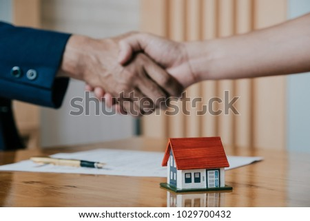 Estate agent shaking hands with his customer after contract signature, Contract document and house model on wooden desk Foto stock ©