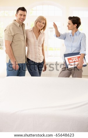Estate agent showing young happy couple around in new house.?