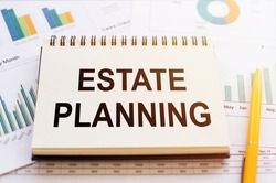 ESTATE PLANNING- written on notepad on financial charts and graphs with yellow pen.