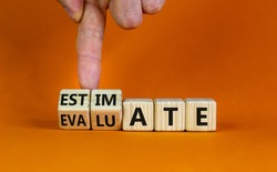 Estimate or evaluate symbol. Businessman turns wooden cubes and changes the word 'evaluate' to 'estimate'. Beautiful orange background, copy space. Business, estimate or evaluate concept.