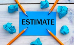ESTIMATE - word on blue paper on a light background with crumpled pieces of paper and pencils. Business concept