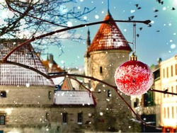 Estonia .Tallinn .winter in old town  red Christmas ball  on tree in city park .snowflakes, medieval houses tower roof ,travel to Europe Estonia romantic background