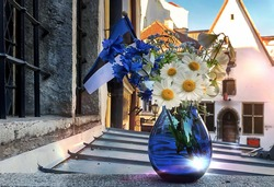 Estonian flag and  blue glass vase with wild blue white cornflowers and daisies  flowers , national Estonia republic symbol   , medieval house roofl windows  in  Tallinn old town Estonia Europe