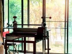 Etching press, art equipment for printmaking. Old red etching press in art studio near glass sliding door on the green garden background outside the building.