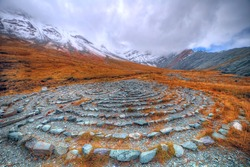 Eternal circles on the ground of stone boulders. Mountain peaks and snow peaks. Ethnic pattern on the ground, a labyrinth of stones.