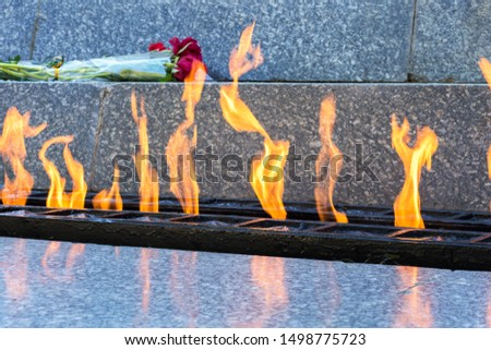 eternal flame, a symbol of memory and heroism. Flames of fire in a marble pedestal and two carnations. Side view