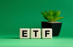 ETF - business concept on a green background. Wooden cubes and flower in a pot.