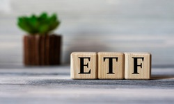 ETF (Exchance Traded Fund) - acronym on wooden cubes against the background of a light board with beautiful divorces and a cactus. Business concept