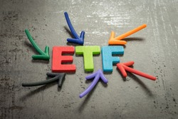 ETF, exchange-traded fund an investment fund traded on stock exchanges concept, multi color arrows pointing to the word ETF at the center of black cement chalkboard wall.