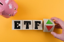 ETF exchange traded fund and red and green arrow symbol on wood cubes besides piggy bank on colored background, investing money concept