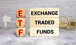 ETF, Exchange Traded Fund, realtime mutual index fund that can trade in equity stock market, cube wooden block with alphabet building the word ETF on grid line paper, random block in the background.