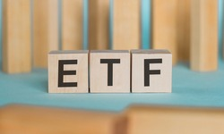 ETF - financial business concept on a blue table with wooden background.