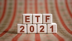 ETF 2021 text on wooden cubes on a monochrome background with reflection.