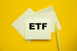 ETF - word on yellow stickers and a paper, yellow PeN on a yellow background. a bright solution for business, financial, marketing concept