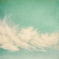 Ethereal and puffy clouds on a vintage paper background.  Image has a pleasing paper grain and texture.