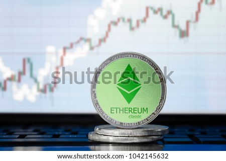 ETHEREUM classic (ETC) cryptocurrency; physical concept ethereum classic coin on the background of the chart