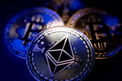 Ethereum Coin and Bitcoin in background. Cryptocurrency ETH and BTC. Tokens Blockchain. High Tech Crypto concept. Decentralized crypto currency Ether