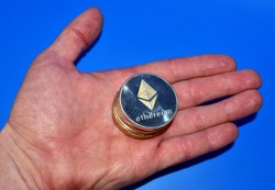 Ethereum coin in hand on blue background. Сryptocurrency trading exchange. ETH mining and investing concept. Blockchain and financial technology. Crypto prices and market capitalization