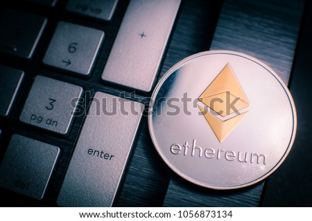 Ethereum cryptocurrency (crypto currency). Silver Ethereum coin with gold Ethereum symbol on a laptop keyboard next to the Enter key