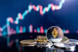 Ethereum (ETH) and other crypto coins with blurred candlestick chart. Ethereum is a decentralized, open-source blockchain with smart contract. Cryptocurrency and decentralized finance concept