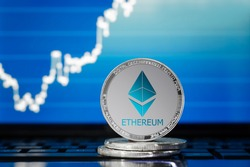 ETHEREUM (ETH) cryptocurrency; silver ethereum coin on the background of the chart