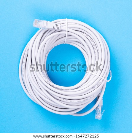 Ethernet cable rolled up, isolated, isolated on blue