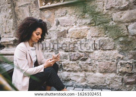 Ethic concentrated female in pink jacket with long curly hair browsing on mobile phone sitting on stairs near ancient building