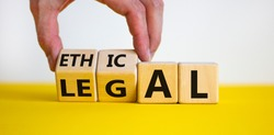 Ethical or legal symbol. Businessman hand turns wooden cubes and changes the word 'legal' to 'ethical' on a beautiful yellow table, white background. Business and ethical or legal concept. Copy space.