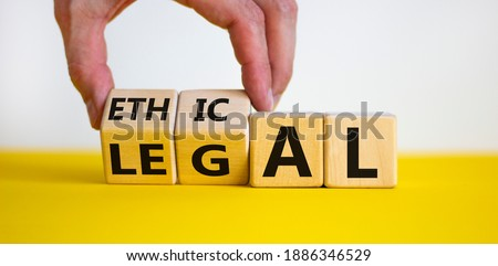 Ethical or legal symbol. Businessman hand turns wooden cubes and changes the word 'legal' to 'ethical' on a beautiful yellow table, white background. Business and ethical or legal concept. Copy space. Stock photo ©
