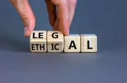 Ethical or legal symbol. Businessman turns wooden cubes and changes the word 'ethical' to 'legal' on a beautiful grey table, grey background. Business and ethical or legal concept. Copy space.