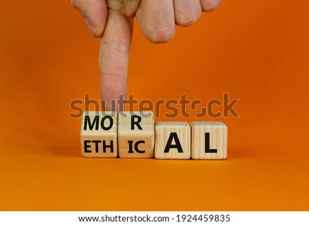 Ethical or moral symbol. Businessman turns wooden cubes and changes the word 'moral' to 'ethical' on a beautiful orange table, orange background. Business and ethical or moral concept. Copy space. Foto d'archivio ©